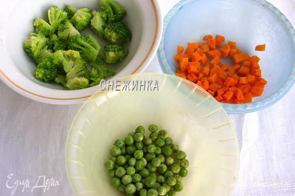 У меня овощи (капуста и горошек) были мороженные, поэтому предварительно их размораживаем. Горошек оставляем, а брокколи опускаем на минуту в кипящую воду и хорошо даём стечь воде. Морковь чистим, нарезаем кубиком и варим со щепоткой соли до полуготовности, около нескольких минут. Откидываем на дуршлаг.