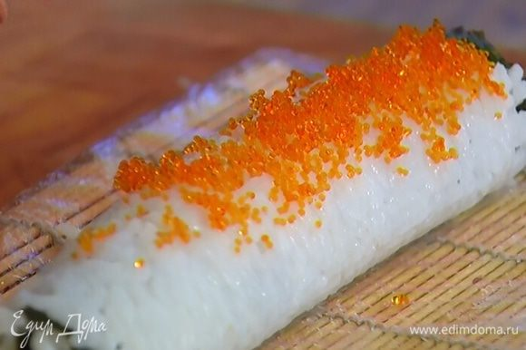 Переложить рисовый рулет с коврика на рабочую поверхность и намазать икрой, а затем порезать на порции.