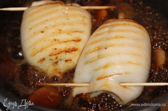 Переложить кальмары в соус и и готовить на сильном огне 2 мин. , 2-3 раза перевернув тушки Снять с огня, вынуть шпажки. Подавать со свежей зеленью.