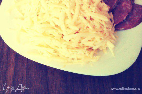 Колбасу нарезать кружочками. Сыр натереть.