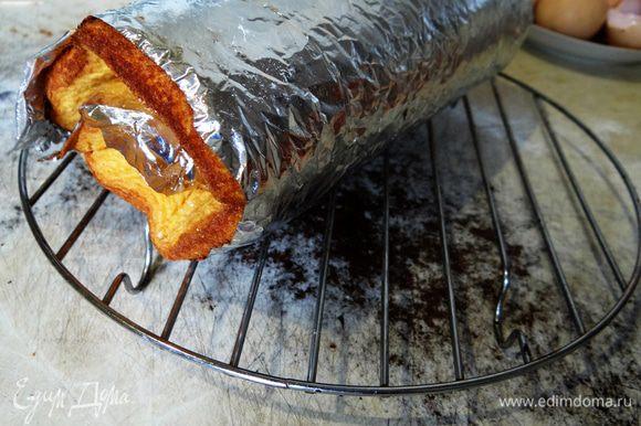 Еще горячий бисквит вместе с бумагой свернуть в рулет и переложить на решетку. Оставить охлаждаться.