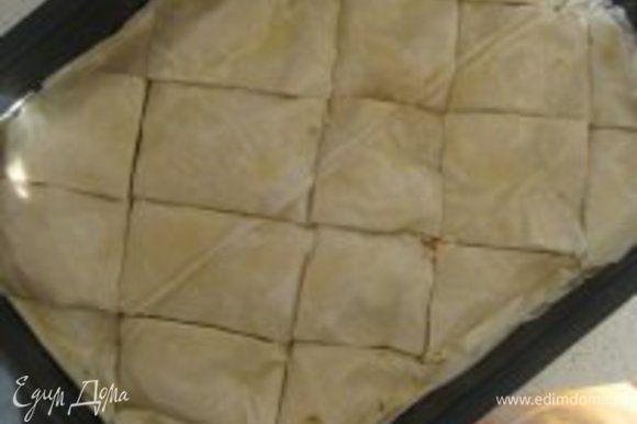 Перед тем как поставить баклаву в духовку, ее необходимо разрезать на ромбики (на половину глубины слоев теста). Выпекать в разогретой до 180 градусов духовке примерно 30 минут, затем увеличить нагрев духовки до 220 градусов и выпекать еще 5 минут