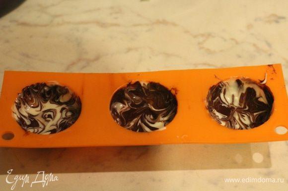 Теперь делаем мраморные конфеты. Белый и темный шоколад по очереди наносим на стенки формы. Теперь формы нужно слегка наклонять и крутить, чтобы шоколад немного перемешался и равномерно распределился по стенкам. Можно перемешать при помощи деревянной шпажки. Охладить 10 минут в морозильной камере.