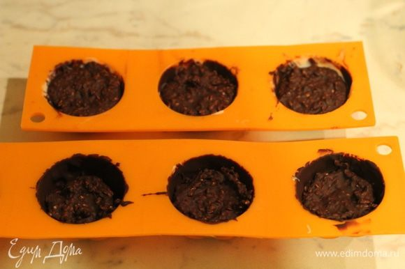 Начинка. Кунжут обжарить на сухой сковороде до золотистого цвета, смешать с частью темного шоколада и слегка охладить. Наполнить конфеты начинкой. Охладить в морозильной камере 10 минут.