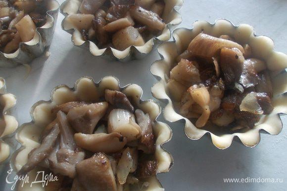 Затем в формочки положить обжаренные грибы. Немного их утрамбовать.