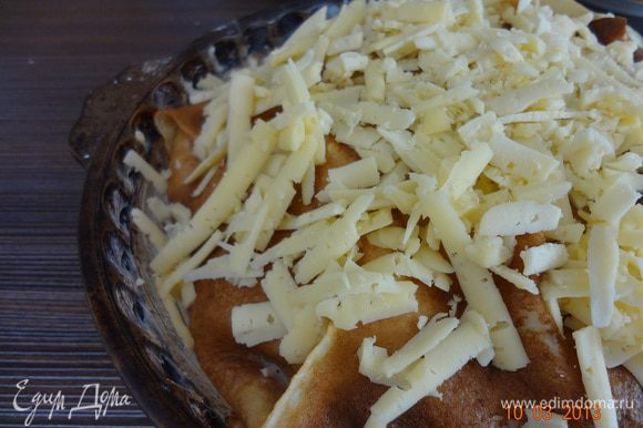 Накрыть верх выступающими краями блинов, полить заливкой, посыпать тертым сыром. Поставить в нагретую предварительно до 180 С духовку на 20-25 минут.