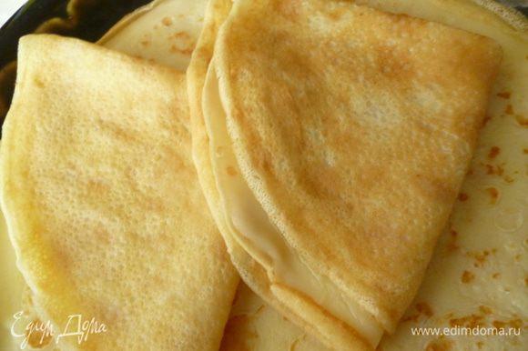 Приготовить блины: Яйца слегка взбить с щепоткой соли,добавить сироп от консервированных ананасов,перемешать.Добавить просеянную муку,хорошо перемешать до однородности,добавить растительное масло,перемешать.Добавить молоко,перемешать.Выпекаем блинчики на хорошо нагретой сковороде. Я выпекаю по старому проверенному мною методу: пеку в чугунной сковороде,которую протираю кусочком сала перед заливкой теста. Вы можете печь по своему.