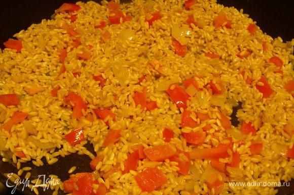 Перец режем кубиками и добавляем вместе с рисом в сковородку. Обжариваем все минуты 3-5, чтобы рис пропитался маслом.