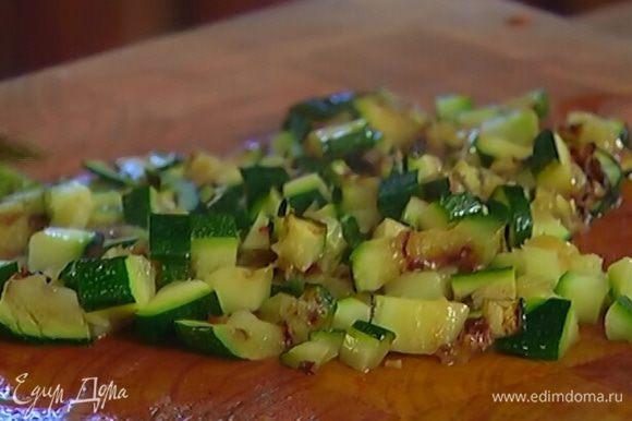 Разогреть в сковороде гриль 1/2 ч. ложки оливкового масла и обжарить полоски цукини с двух сторон, затем нарезать небольшими кусочками.