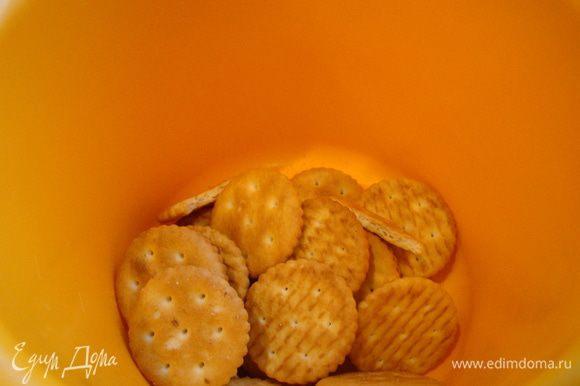 Орехи перемешать с дроблеными крекерами, 1/3 (или 1/4 ) массы отложить, а оставшиеся плотно утрамбовать в выстеленную пергаментом форму 22 см, поставить в холод