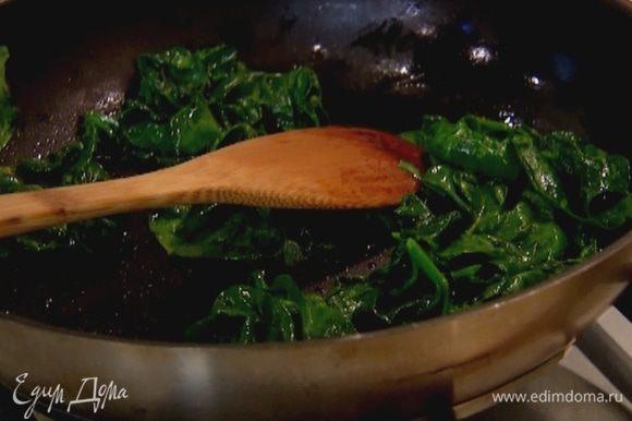 Разогреть в сковороде оливковое масло, выложить шпинат и слегка прогреть его на медленном огне, чтобы он поплыл.
