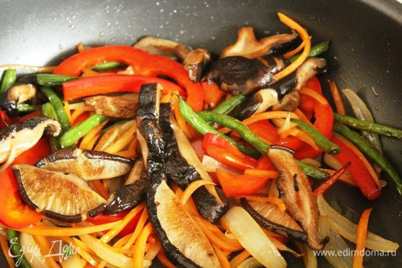 На этом же масле обжарить лук, морковь, болгарский перец, фасоль и грибы, добавляя их поочередно. Добавить креветки, хорошо перемешать, влить остатки маринада для загустения соуса, добавить крахмал и кунжутное масло.