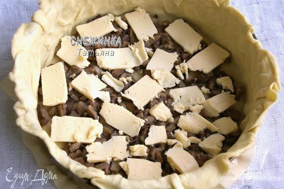 На дно кладём грибы, которые кусочками, на них нарезаем полоски плавленого сыра.