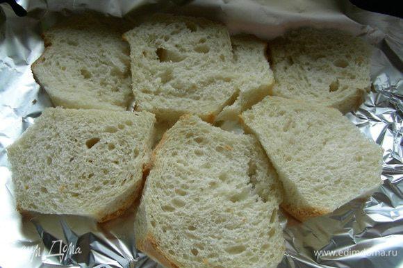 Хлеб режем ломтиками и срезаем корки. Выкладываем его на противень, застеленный бумагой для выпечки.