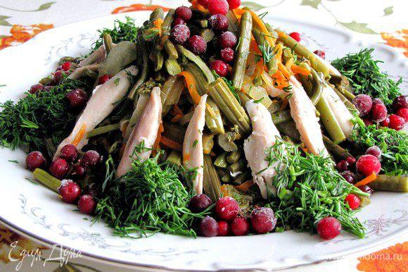 Затем собираем салат. На блюдо или в салатницу выкладываем горкой пассерованные овощи, сверху крупно нарезанное куринное филе. Посыпаем салат свежей или замороженной брусникой на ваш вкус, побольше или поменьше. Украшаем зеленью. Подаем к столу, пробуем. Очень вкусно!