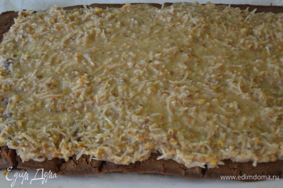 Затем развернем и выложим приготовленную кокосовую начинку с пеканом,распределяя по всей поверхности. Свернем в рулет и переложим в хлебную форму вытягивая бумагу для выпечки осторожно.