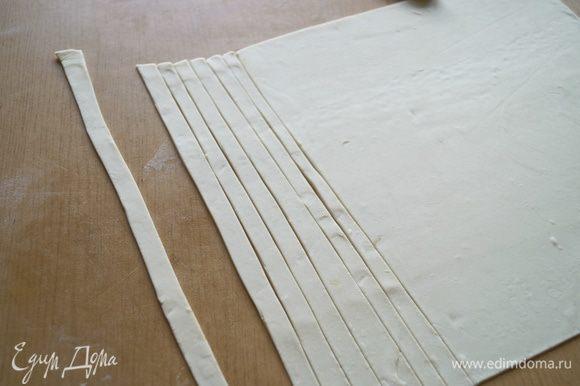 Готовое слоеное тесто разморозить и тонко раскатать, после чего нарезать длинными полосками шириной примерно 1 см.