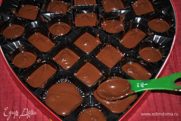 Ложкой растопленный шоколад разложим по ячейкам. Поставим на несколько минут в холодильник.Достанем из холодильника.