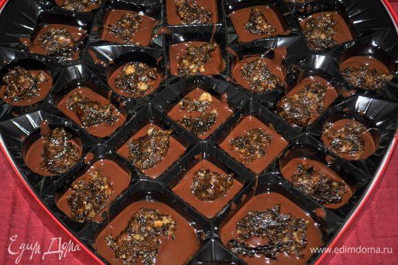 Затем начинку небольшими порциями разложим по конфетным ячейкам.