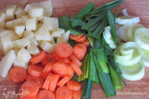 Белую часть лука-порея нарезать колечками, зелёную-полосками. Морковь нарезать кружочками, картофель-ломтиками. Зелень мелко порезать.