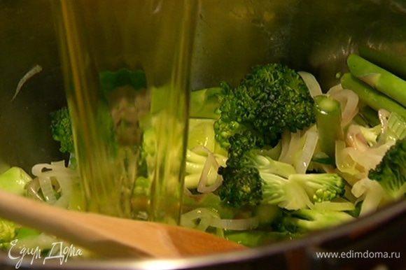 Отправить брокколи и спаржу в кастрюлю с луком и чесноком, перемешать и залить горячим овощным бульоном, так чтобы все овощи были покрыты.