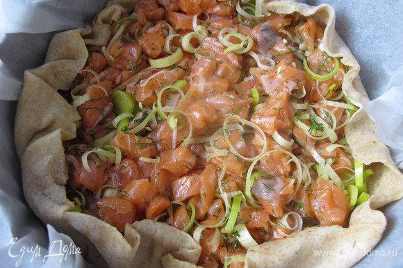 На подсушенное тесто выкладываем лосось, лук и укроп, чуть солим и перчим.