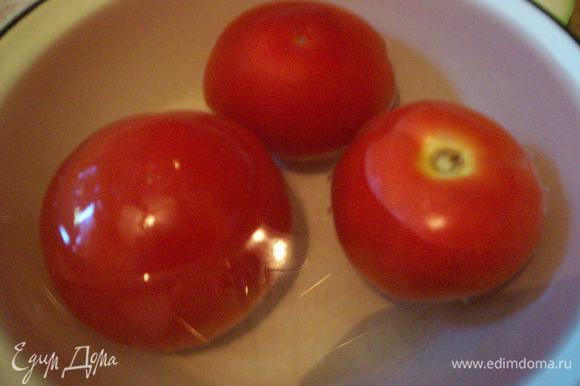 Снимаем с помидоров шкурку. Для того, чтобы сделать это быстро и легко, обдаем их крутым кипятком и оставляем в воде на полминуты - после такой тепловой обработки шкурка слезает очень легко. Режем помидоры на дольки.
