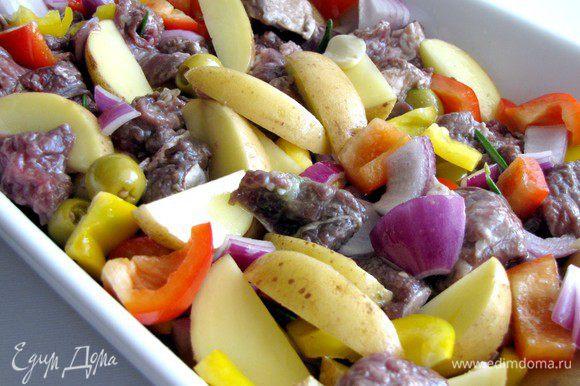 В смазанный оливковым маслом противень выложить овощи, добавить мясо оливки. Перемешать.