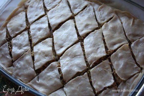 На последний слой начинки кладем листочек, смазываем его сливочным маслом и кладем еще один листочек. Сверху все смазываем сливочным малом и нарезаем пахлаву ромбами. После выпечки это будет очень трудно сделать.