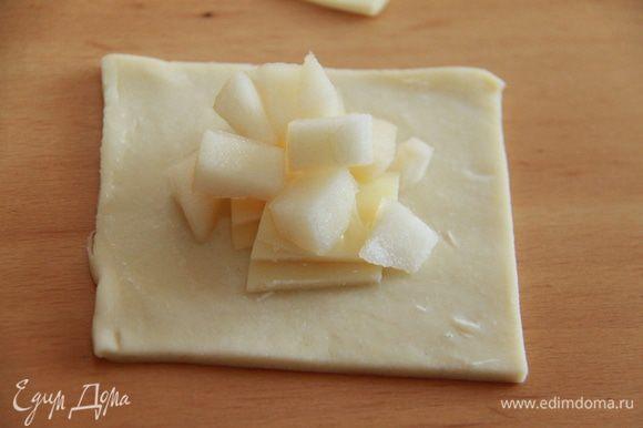 Края квадрата смазываем белком (или яйцом). В центр квадрата кладём сыр и грушу. Соединяем края по диагонали и прижимаем.