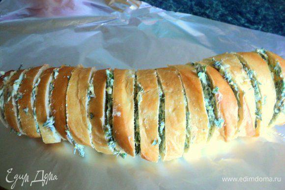 Багет надрезать, не доходя до края, на кусочки толщиной 1.0-1.5 см. Щедро промазать кусочки маслом с зеленью.