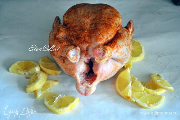 Курицу вымыть. Натереть специями и солью. Лимон порезать на не тонкие дольки и нафаршировать ими курицу. Ничем брюшко курочки не зашивать.