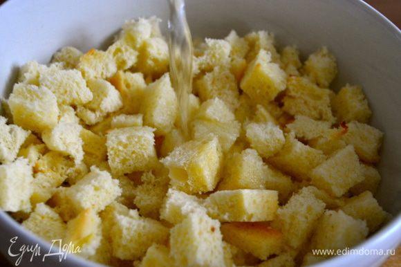 Хлеб нарезать кубиками, сложить в миску и залить водой. Отставить в сторону на минут 30.