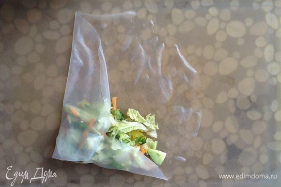 Рисовый блинчик замочить в теплой воде на 15-20 секунд, выложить на доску или тарелку. На блинчик положить овощную начинку и завернуть классическим способом.
