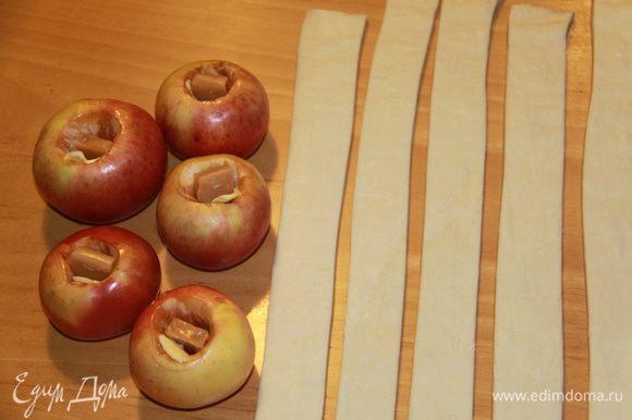 """Подготовить яблоки: вымыть, удалить сердцевину, но не прорезая дно. Внутрь каждого яблока кладём кусочек масла и ириску (у меня """"Кис-кис""""). Тесто нарезаем на полоски."""