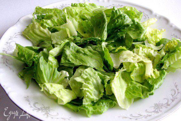 В тарелку выложить салатные листья.