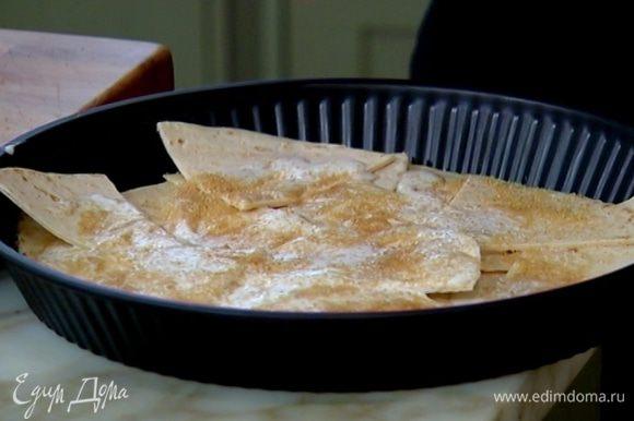Кусочки тортильи выложить в форму для выпечки, полить сливками, посыпать сахаром и отправить в разогретую духовку на 7–10 минут.