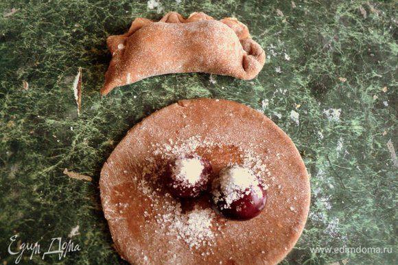 На кружок теста положить по 2-3 вишенки, насыпать немного сахаром и слепить вареники.