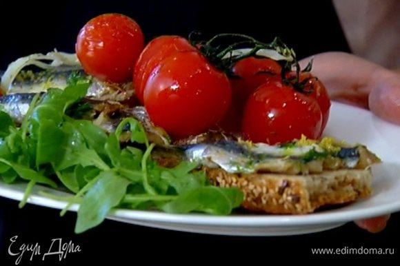 Запеченные сардины выложить на хлеб, подавать с запеченными помидорами и листьями салата.