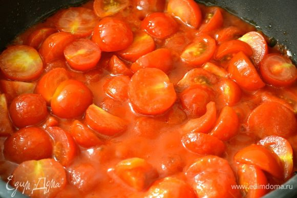Помидорки-черри помыть и нарезать пополам. В глубокой сковороде разогреть оливковое масло, положить помидорки и томатный соус, посолить и поперчить по вкусу. Тушить на огне около 20 минут, время от времени помешивая.