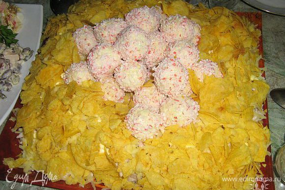 сырные шарики обвалять в крошках крабовых палочек и выложить в центр салата поверх чипсов