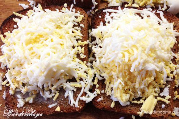 На мелкой терке натереть пол яйца на каждый бутерброд. Слегка посолить.