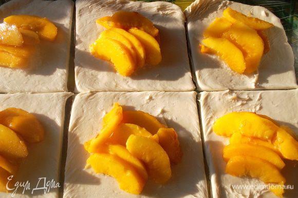 Тесто разрезать на несколько квадратов (у меня вышло 6). На каждый выложить 1 ч л сахара и дольки персиков.