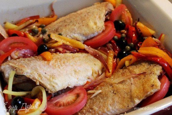На рыбу выложить тушёные овощи, дольки помидоров, маслины и каперсы. Запекать рыбу при 180*С около 8-10 минут.