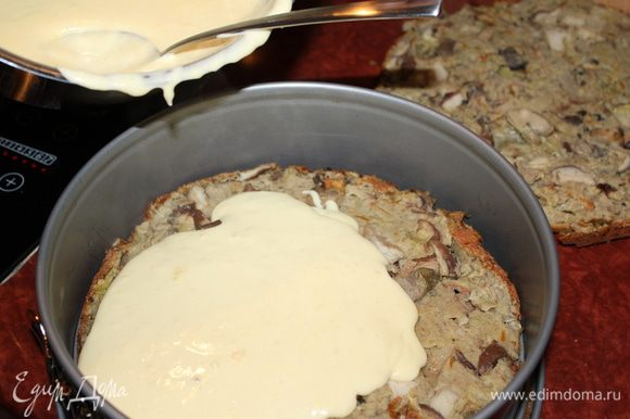 Остывший бисквит разрезать вдоль и уложить в форму. Полить горячим сырным соусом. Уложить вторую половину бисквита и полить оставшимся соусом. Пространство по периметру тоже заполнить соусом.