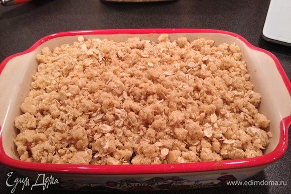 Выложить крошку из теста на фрукты и запекать в духовке 15-20 минут, до румяной корочки.