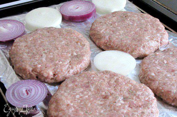 Выложите лук на противень к гамбургерам.