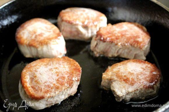 Свиную вырезку нарезать на медальоны и быстро обжарить на горячей сковороде на растительном масле до золотистого цвета. Присыпать мясо солью, перцем, переложить в жаропрочную форму и поставить в духовку, разогретую до 170-180*С на 10-15 минут.