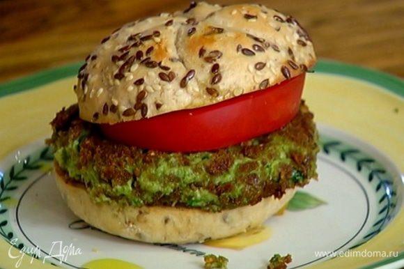На нижнюю половину булок выложить овощную котлету, сверху кружок помидора и накрыть верхней половиной.