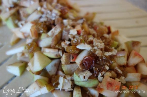 На яблоки равномерно распределить изюм и орехи и посыпать еще 40 г сахара.
